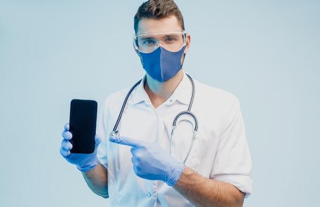 Европейский мужчина-врач показывает мобильный телефон. молодой человек со стетоскопом в белом халате, очках, защитной маске и латексных перчатках. серый фон с бирюзовым светом. студийная съемка. скопируйте пространство.
