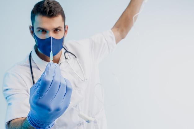 Европейский мужской доктор показывает шприц. молодой человек со стетоскопом в белом халате, защитной маске и латексных перчатках. изолированные на сером фоне с бирюзовым светом. студийная съемка. скопируйте пространство.