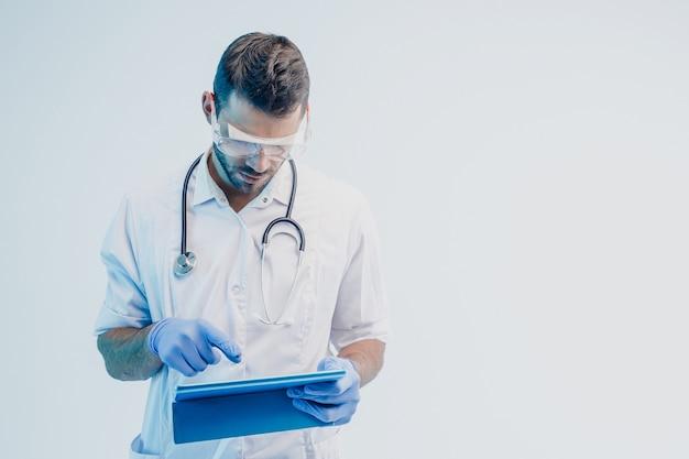 Европейский мужчина-врач с помощью цифрового планшета. молодой бородатый мужчина со стетоскопом в белом халате, очках и латексных перчатках. изолированные на сером фоне с бирюзовым светом. студийная съемка. скопируйте пространство.