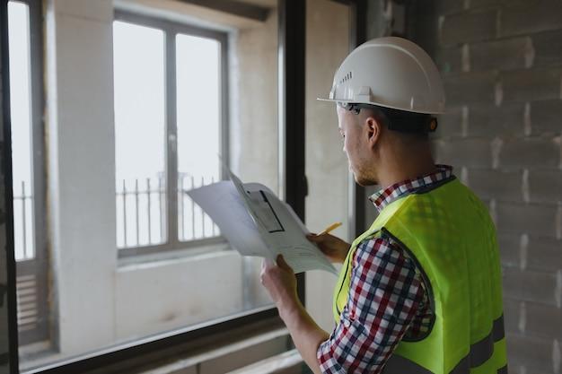 Европейский инженер-мужчина в белом шлеме и жилете безопасности на строительной площадке изучает