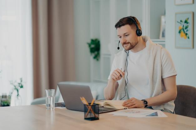 Европейский студент мужского пола изучает иностранные языки онлайн, имеет видеоурок, использует современную гарнитуру, ориентированную на экран ноутбука, компьютер участвует в конференции, слушает лекцию, внимательно делает записи в дневнике