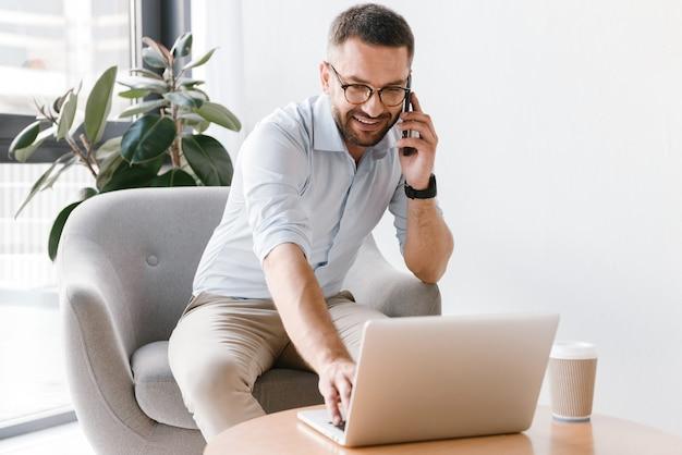 안락의 자에 앉아 노트북을 사용하는 흰색 셔츠에 유럽 남자 30 대, 비즈니스 전화를하는 동안