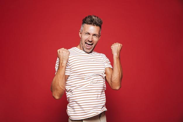 Европейский мужчина в полосатой футболке кричит и сжимает кулаки, изолированные на красном