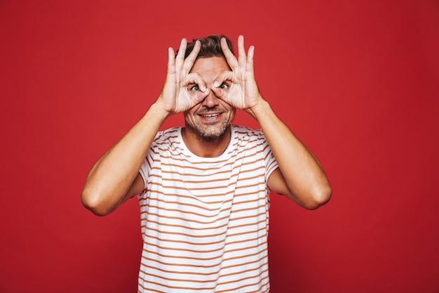 Европейский мужчина в полосатой футболке улыбается и смотрит сквозь дыры, сделанные пальцами, изолированными на красном