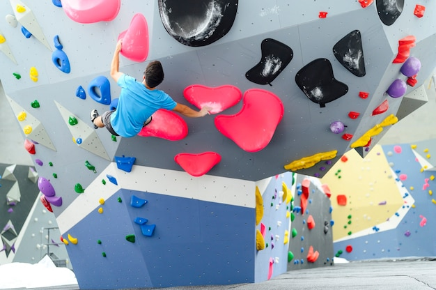 European man rock climber hanging on a wall indoors at the gym