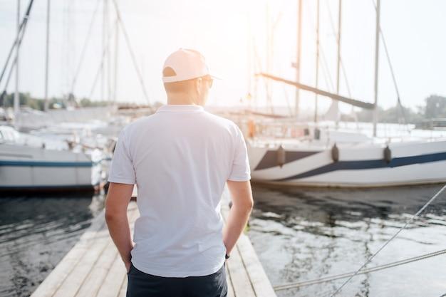 Европейский мужчина стоит на пристани и смотрит на яхту. он держит руки в карманах. молодой человек смотрит налево. он серьезен и спокоен