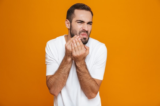 European man in t-shirt touching his cheek and suffering from toothache while, isolated on yellow