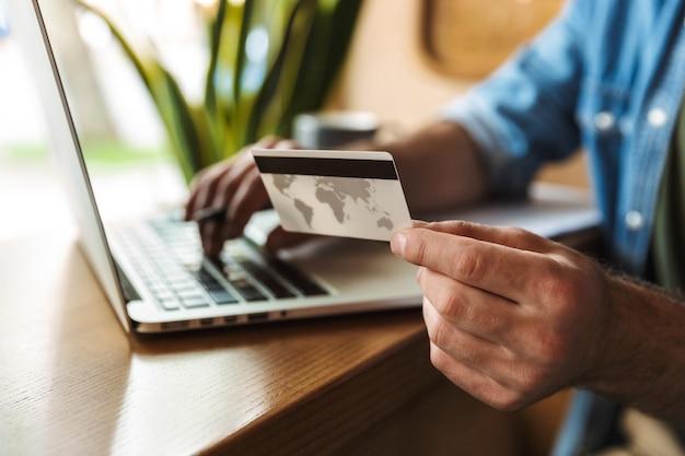 Европейский мужчина в джинсовой рубашке держит кредитную карту и печатает на ноутбуке во время работы в кафе в помещении