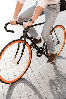 도시 거리에서 자전거를 타고 공식적인 옷을 입고 유럽 남자