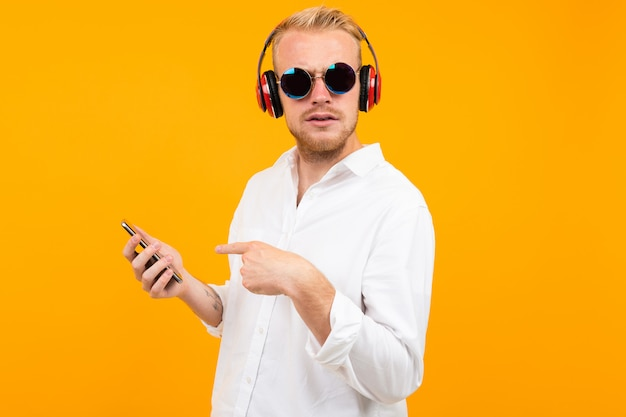 European man in a white shirt and sunglasses listens to music in large headphones on yellow.