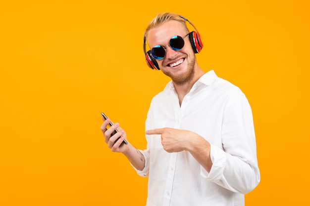 European man in a white shirt and sunglasses with a phone listens to music in large headphones isolated yellow.