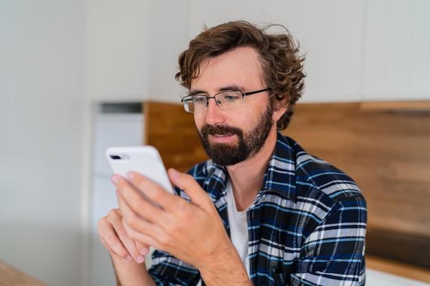 Uomo europeo con la barba utilizzando il telefono cellulare in cucina.
