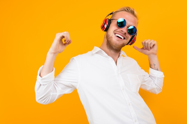 European men in a white shirt and sunglasses listens to music in large headphones on yellow.