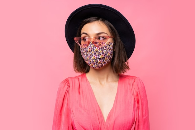 European model dressed protective stylish face mask. wearing black hat and sunglasses. posing over pink wall