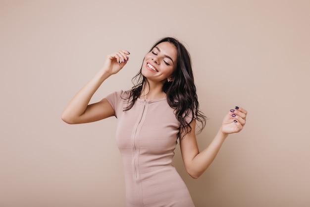 기분 좋은 유럽 모델은 느긋하게 춤을 추고 있습니다. 음악을 즐기고 웃고있는 유행 복장 소녀