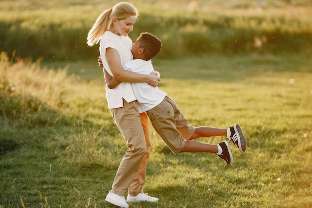 Madre europea e figlio africano. famiglia in un parco estivo.