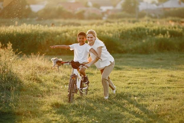 Европейская мать и африканский сын. семья в летнем парке. малыш с велосипедом.