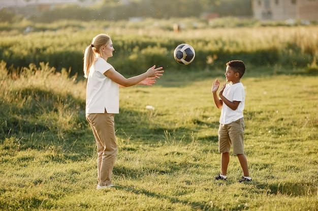Европейская мать и африканский сын. семья в летнем парке. люди играют с мячом.