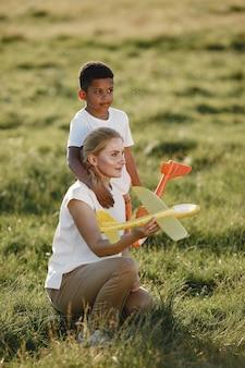 Европейская мать и африканский сын. семья в летнем парке. люди играют с самолетом.