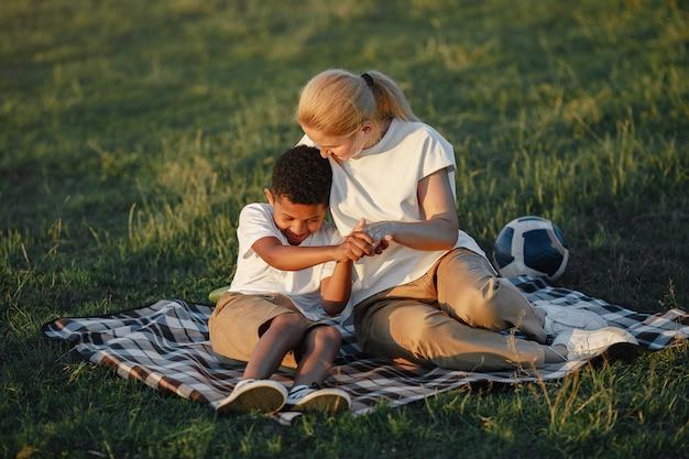 Европейская мать и африканский сын. семья в летнем парке. люди сидят на одеяле.