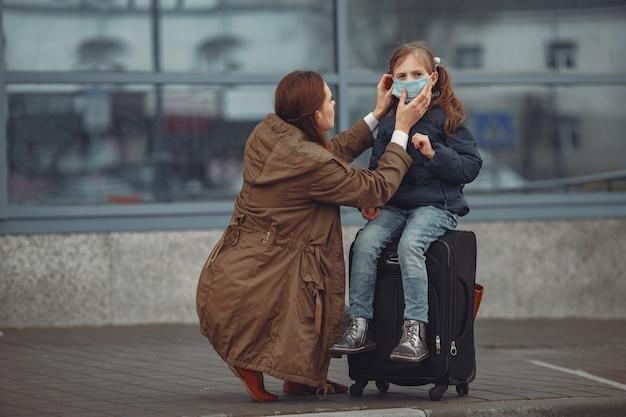 Una madre europea in un respiratore con sua figlia è in piedi vicino a un edificio. il genitore insegna a suo figlio come indossare una maschera protettiva per salvarsi dal virus