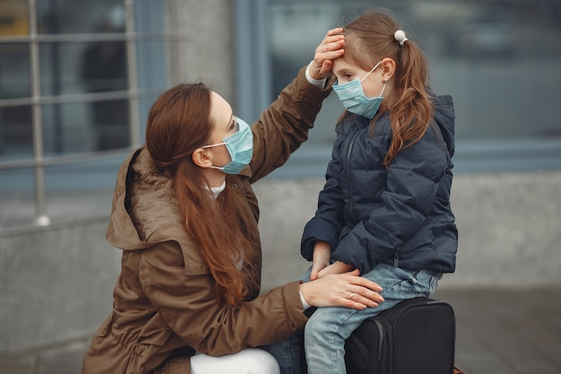 A european mother in a respirator with her daughter are standing near a building.the parent is teaching her child how to wear protective mask to save herself from virus