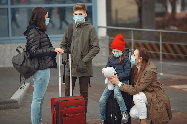 European mothers in respirators with kids are standing near a building.