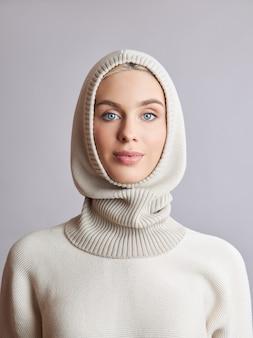 그녀의 머리에 옷을 입고 보닛 후드에 금발 머리를 가진 유럽 이슬람 여성. 부드러운 피부, 천연 화장품을 가진 스웨터를 입은 아름다운 소녀