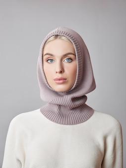 ボンネットフードのブロンドの髪を持つヨーロッパのイスラム教徒の女性は彼女の頭に身を包んだ。