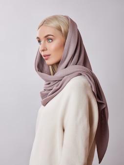 Европейская мусульманская женщина с белокурыми волосами в платке платка оделась на голове. красивая девушка в свитере с мягкой кожей, натуральная косметика