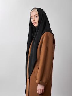 彼女の頭に身を包んだスカーフショールでブロンドの髪を持つヨーロッパのイスラム教徒の女性。