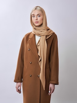 European muslim woman with a blonde hair in a headscarf shawl dressed on her head. beautiful girl in coat with soft skin,.