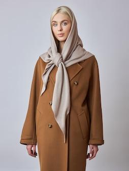 European muslim woman with blonde hair in a headscarf shawl dressed on her head