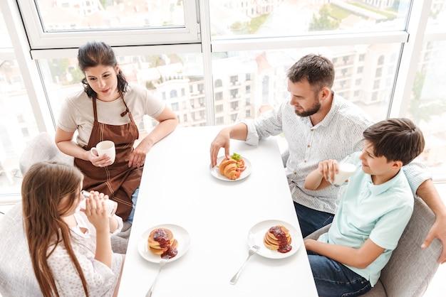 Европейцы родители с детьми 8-10 вместе завтракают на светлой кухне дома, едят круассаны и блины