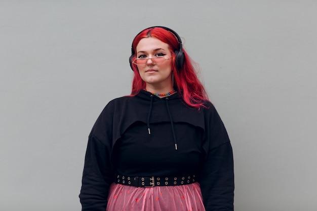 ヘッドフォンでヨーロッパのプラスサイズの女性若い赤ピンクの髪のボディポジティブな女の子