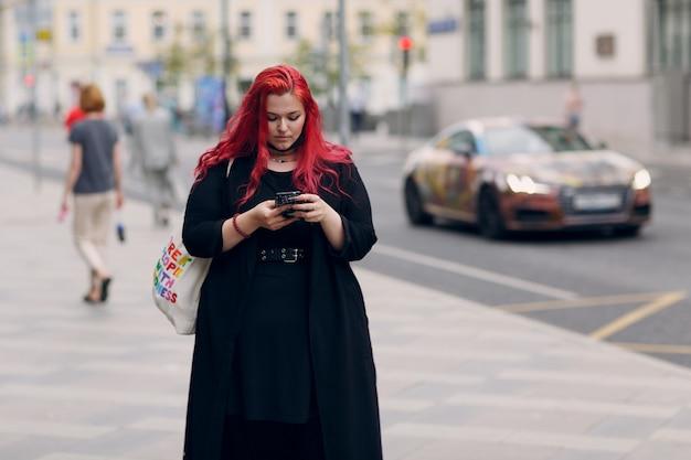 Европейская женщина больших размеров гуляет по улице города с мобильным мобильным телефоном с молодыми рыжими розовыми волосами ...