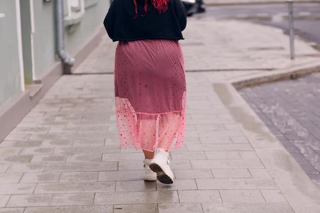 Европейская женщина больших размеров молодая рыжая бодипозитивная девушка гуляет по городской улице в розовом платье