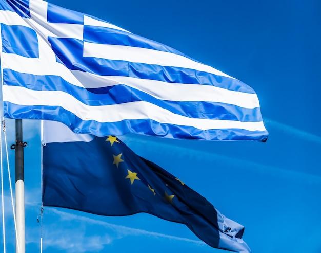 ヨーロッパの青空の背景の政治に関するギリシャと欧州連合のヨーロッパの政治ニュースのギリシャと国家の概念の旗