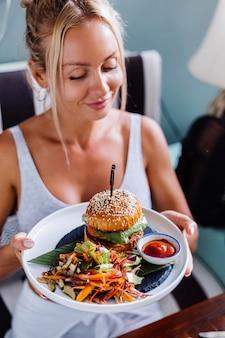 여름 카페에서 달콤한 햄버거에 배고픈 유럽 예쁜 여자