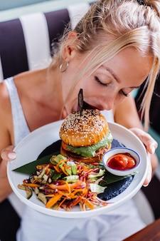 夏のカフェでジューシーなハンバーガーに飢えているヨーロッパのきれいな女性
