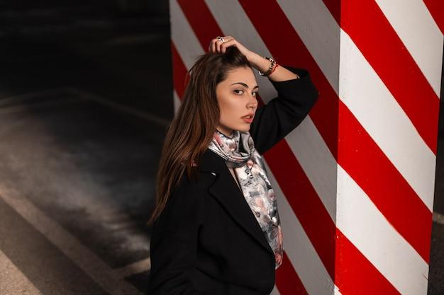 スタイリッシュでエレガントなシルクスカーフのファッショナブルな黒のコートで茶色の髪を持つヨーロッパのかなり若い女性は、都市の駐車場のモダンな赤白の柱の近くでリラックスしています。都会的な魅力的な女の子のファッションモデル。