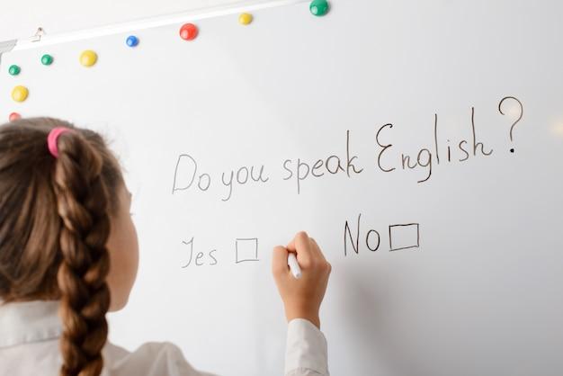 Европейский ученик начальной школы пишет на доске