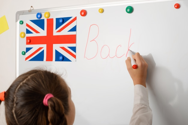 European pupil of primary school writing on whiteboard