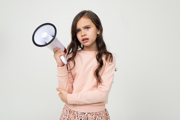 European serious girl with a megaphone on a white studio wall with blank space