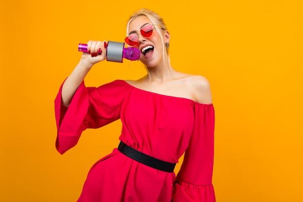 Европейская сексуальная девушка ведет мероприятие в красном платье с открытыми плечами с микрофоном в руках