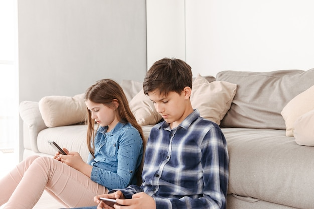 European siblings girl and boy sitting on floor near sofa at home, and both using smartphone