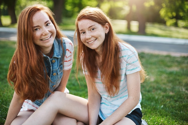 European sisters with red hair and freckles sitting on green grass and smiling broadly, hanging out with friends on picnic, expressing joy and amusement. emotions and family concept