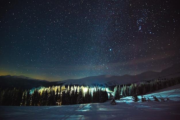 美しい星空を背景に夜の絵のように美しい森の山の丘の間に位置する、蒸気と煙のあるヨーロッパのスキーリゾート。冬の休暇のコンセプト。コピースペース