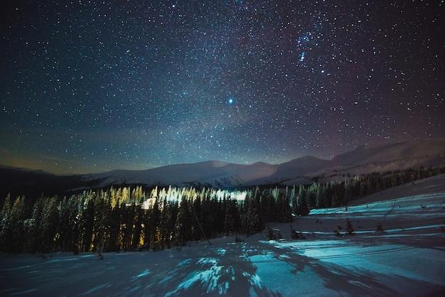 Европейский горнолыжный курорт с паром и дымом, расположенный среди живописных лесных горных холмов ночью на фоне красивого звездного неба. концепция зимних каникул. copyspace