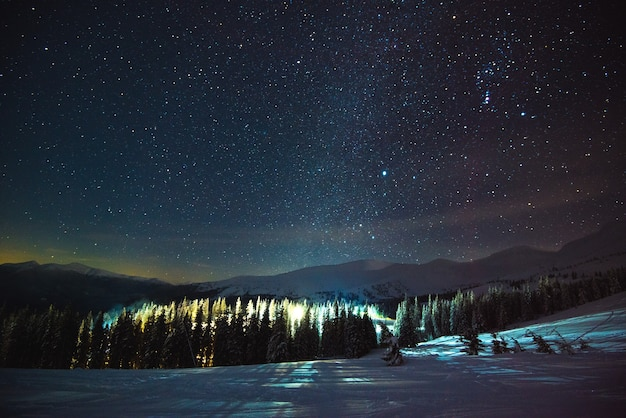 European ski resort with steam and smoke, located among the picturesque forest mountain hills at night against a beautiful starry sky. winter vacation concept. copyspace